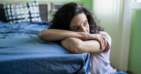 Worried woman sitting on floor next to bed