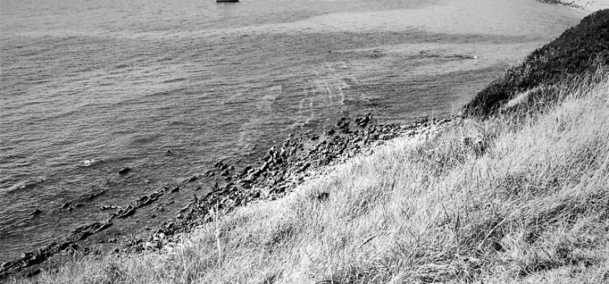 grayscale-photography-of-boat-on-body-of-water-near-mountain-949502