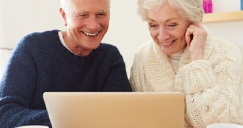 senior couple with coffee at the laptop- website
