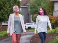Two women wearing protective face masks enjoying the outdoors during Coronavirus