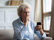 Thoughtful middle aged hoary woman holding smartphone, reading news.